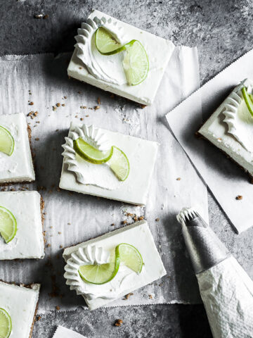 Squares of white cheesecake bars on parchment paper on a grey stone surface