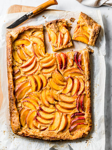 A golden brown rectangular peach galette rests atop whipte parchment paper on a wooden cutting board. Two squares are cut out of the top right corner with a wooden handled paring knife.