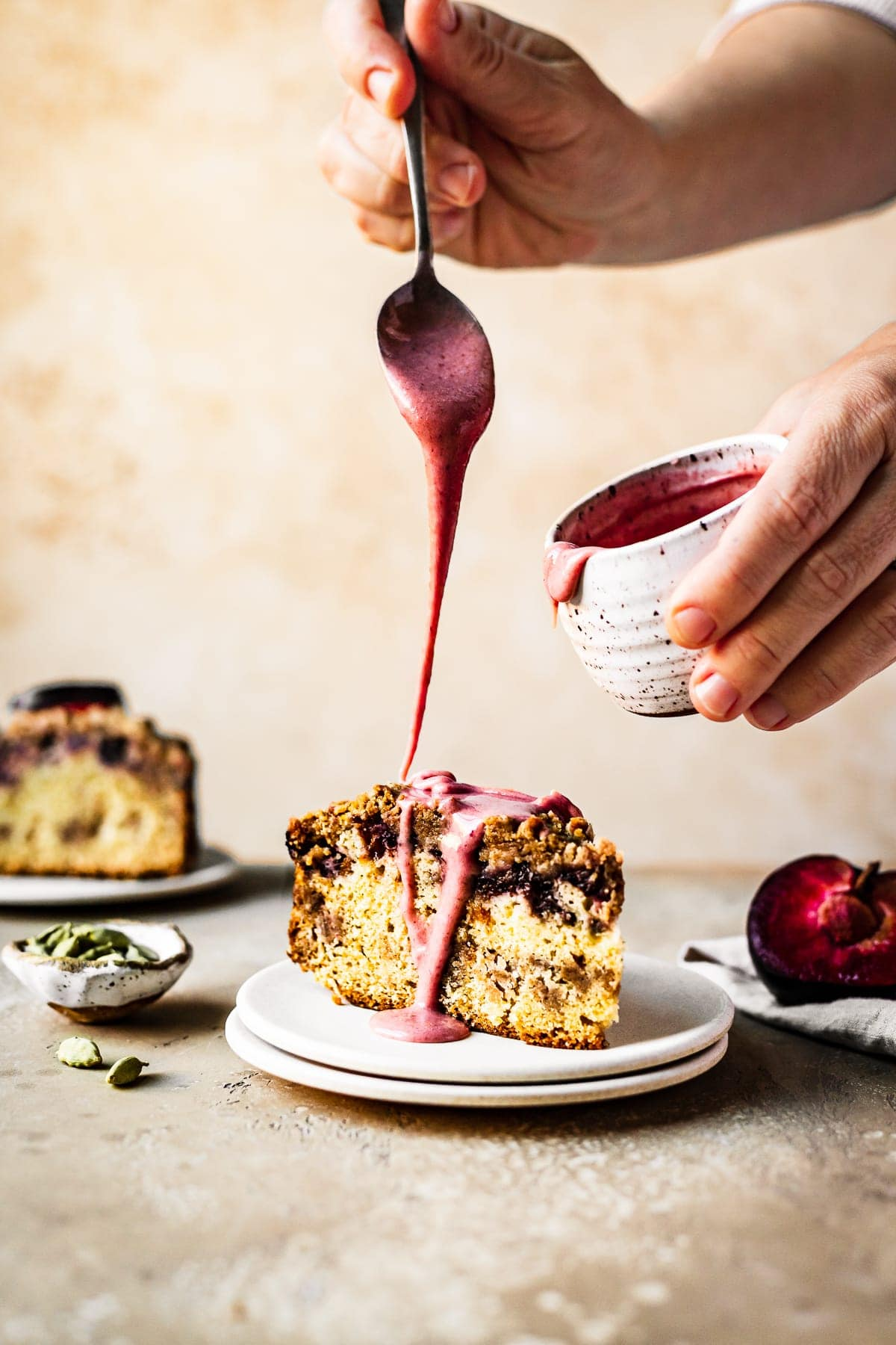 Hands reach into the frame drizzling a spoonful of pink glaze onto a slice of coffee cake. The other hand holds a white speckled ceramic jar of glaze. The surface and background are both a warm tan color. Resting next to the cake slice is half a plum, a small bowl of cardamom pods, and a slice of cake in the background.