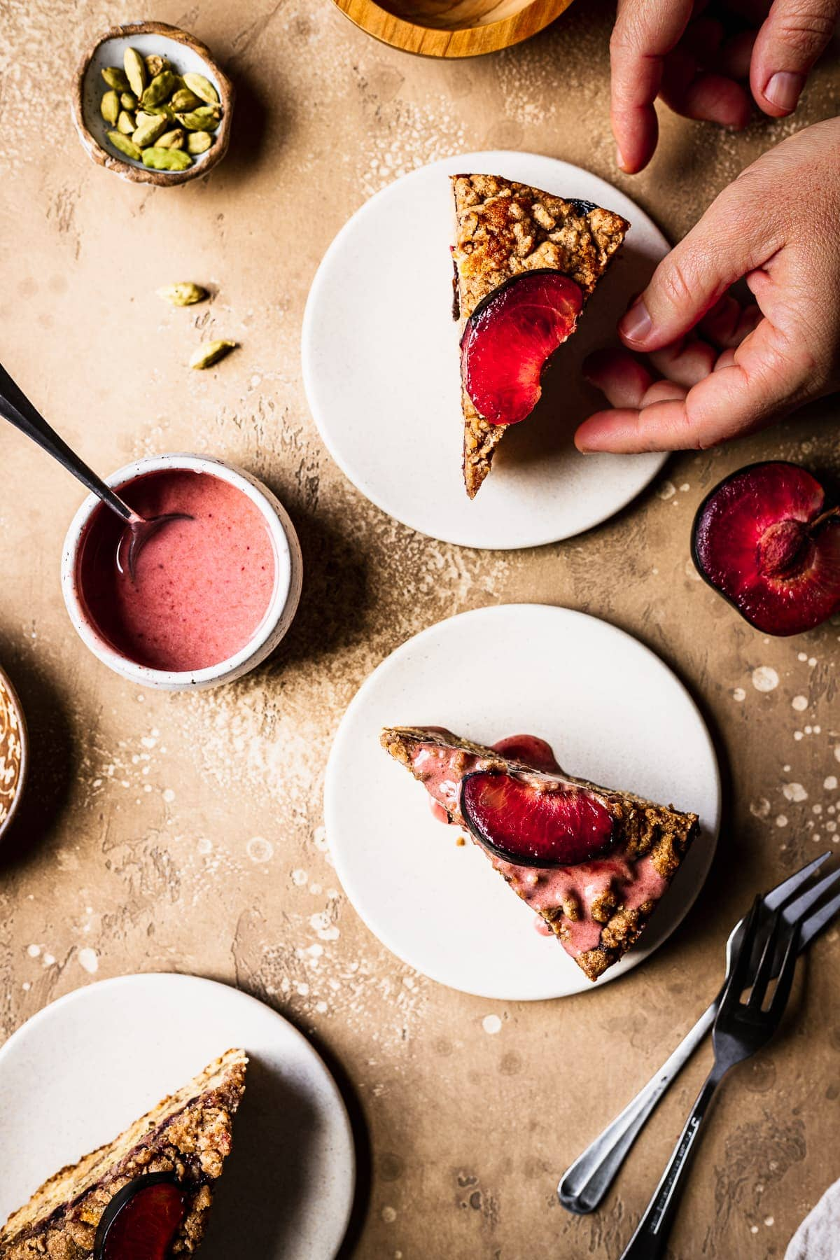 Hands reach into the frame towards slices of cake on light colored ceramic plates topped with plum slices. The background is a warm tan color. Surrounding the cake slices are forks, sliced plum halves, a bowl of pink glaze, and a small bowl of green cardamom pods.