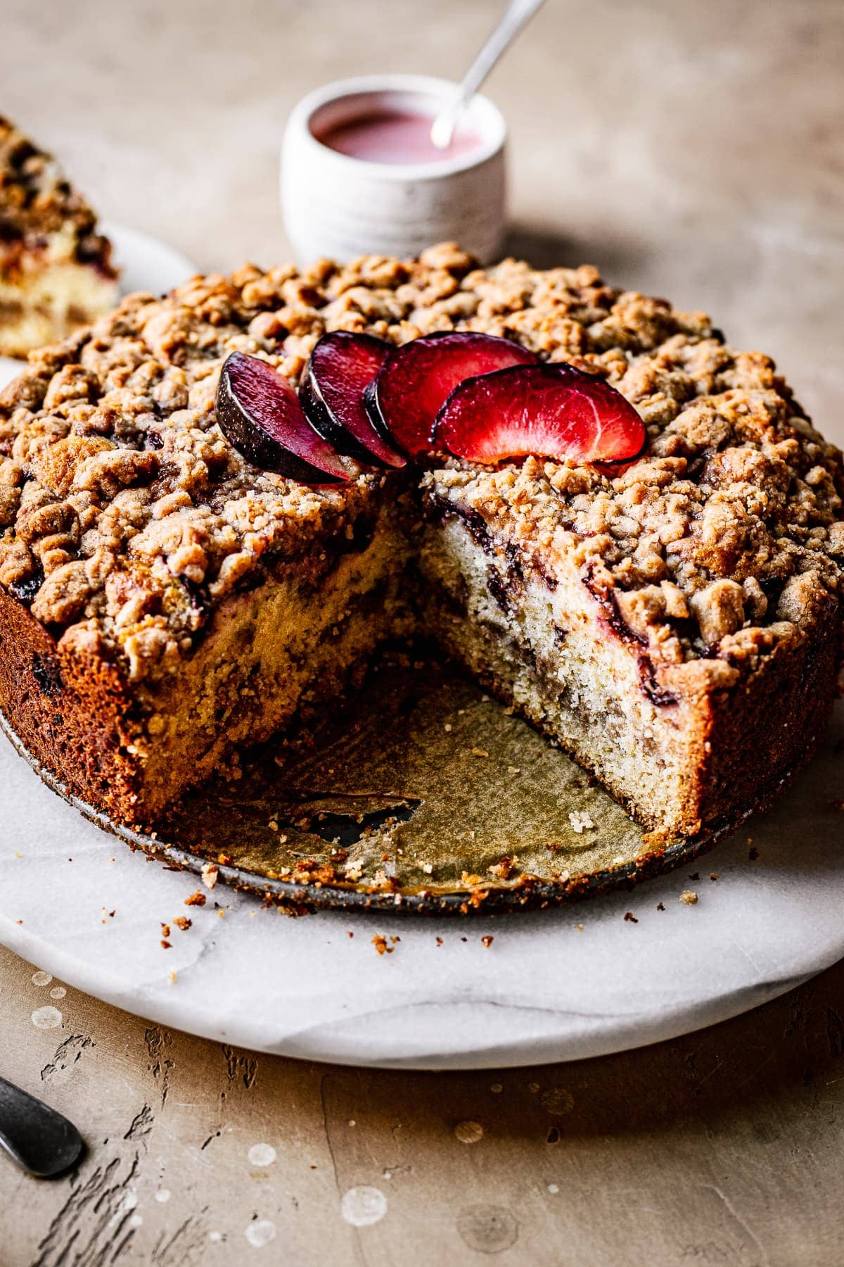 A round coffee cake with several slices cut out of it on a marble platter on a warm tan surface. There is a fan of sliced plums on top of the cake. In the background is a slice of cake and a white ceramic container of pink glaze.