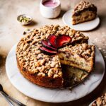 A round coffee cake with several slices cut out of it on a marble platter on a warm tan surface. There is a fan of sliced plums on top of the cake. Nearby are several slices on small plates, a container of pink glaze, and a small bowl of green cardamom pods.
