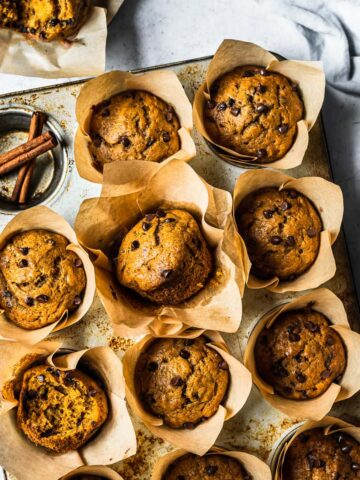 Baked pumpkin banana muffins in brown parchment liners in a muffin tin on a white stone surface. Surrounded by an opened muffin, a blue linen, a d a small ceramic bowl of chocolate chips.