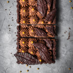 A rectangular chocolate tart with piped chocolate over layers of caramel in a chocolate pastry shell. There are decorative chocolate pastry leaves on top. It is resting on a grey textured surface.